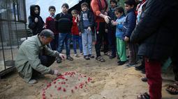 Pemilik kebun binatang Fathi Jumaa menaburkan bunga di kuburan empat anak singa di kebun binatangnya di kamp pengungsi Rafah, Gaza (18/1). Empat anak singa tersebut tewas pada pagi hari jelang berlangsungnya badai musim dingin.  (AP Photo/Adel Hana)