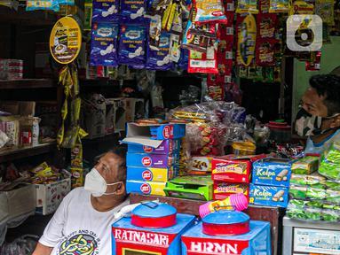 Warga menonton televisi yang menayangkan penyuntikan vaksin COVID-19 terhadap Presiden Joko Widodo atau Jokowi di Jakarta, Rabu (13/1/2021). Jokowi menjadi orang pertama di Indonesia yang disuntik vaksin COVID-19 produksi Sinovac. (Liputan6.com/Faizal Fanani)
