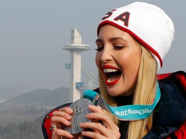 Ivanka Trump memegang medali perak milik bobsleigh wanita AS Lauren Gibbs selama acara bobsleigh pria empat orang Olimpiade Musim Dingin Pyeongchang 2018 di depan menara lompat ski di Pyeongchang (25/2). (AFP Photo/Pool/Eric Gaillard)