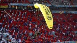 Paraglider Greenpeace mendarat di stadion sebelum pertandingan Grup F Euro 2020 antara Prancis dan Jerman di Allianz Arena, Munich, Jerman, Selasa (15/6/2021). Sang aktivis hampir kehilangan kendali paraglidernya dan hampir menabrak para penonton. (AP Photo/ctivist Alexander Hassenstein, Pool)