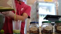 Pekerja membuat ramuan jamu tradisional di kafe Suwe Ora Jamu, kawasan M Bloc, Jakarta, Jumat (10/7/2020). Sejumlah orang masih mengonsumsi jamu sebagai salah satu cara untuk menjaga daya tahan tubuh di tengah pandemi COVID-19 seperti saat ini. (Liputan6.com/Herman Zakharia)