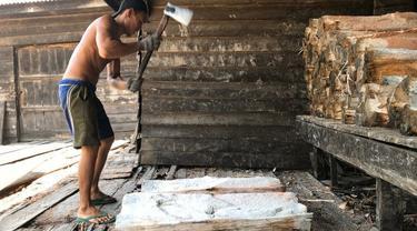Seorang pekerja di kilang sagu mengupas tual sagu untuk diolah menjadi sagu basah.