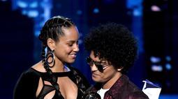 Penyanyi Bruno Mars menerima trofi Record of the Year dari Alicia Keys pada ajang Grammy Awards 2018 di New York City, Minggu (28/1). Dengan album 24K Magic, Bruno merebut enam trofi Grammy termasuk Record of the Year. (Kevin Winter/Getty Images/AFP)