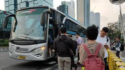 Warga menaiki angkutan umum di tepi Jalan Jenderal Sudirman, Jakarta, Senin (8/7/2019). Tidak adanya halte tersebut mengurangi kenyamanan serta mengganggu arus lalu lintas. (Liputan6.com/Immanuel Antonius)