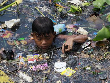 Seorang Anak laki-laki memilah sampah yang terapung untuk di jadikan bahan daur ulang di sebuah sungai yang tercemar di kota navotas, Manila, Kamis (2/7/2015). Daur ulang bertujuan untuk mengurangi tingkat pencemaran sungai. (REUTERS/Romeo Ranoco)