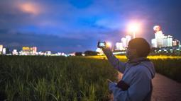 Seorang anggota tim medis Beijing mengabadikan foto di Taman Jiangtan Hankou di Wuhan, Provinsi Hubei, China tengah, pada 26 Maret 2020. Seiring meredanya wabah virus corona (Covid-19), kehidupan di Wuhan berangsur-angsur kembali normal. (Xinhua/Xiao Yijiu)