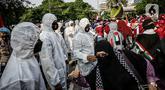 Petugas Satgas COVID-19 dari personel kepolisian menjaga protokol kesehatan peserta aksi solidaritas untuk Palestina di depan Kedutaan Besar Amerika Serikat, Jakarta, Selasa (18/5/2021). Massa mengutuk dan mengecam keras kekerasan yang dilakukan Israel atas Palestina. (Liputan6.com/Faizal Fanani)