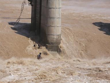 Dua nelayan terjatuh di tengah banjir setelah tali putus saat operasi penyelamatan gagal menggunakan helikopter Angkatan Udara India di Sungai Tawi di Jammu, India (19/8/2019). Kedua nelayan tersebut selamat kemudian berenang ke tempat yang aman. (AP Photo/Channi Anand)