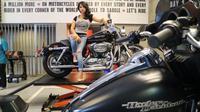 Seorang wanita berpose di atas salah satu motor Harley-Davidson