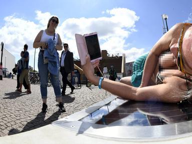 Lena Salmi mengisi baterai ponselnya saat berjemur di bangku panel surya di Helsinki, Finlandia, (9/7). Bangku panel surya dapat digunakan untuk mengisi ulang sepeda listrik dan perangkat mobile. (AFP Photo/Lehtikuva/Martti Kainulainen)
