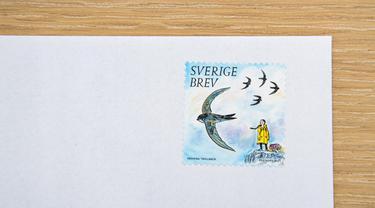 Prangko hasil ilustrasi seniman Swedia Henning Trollback yang menggambarkan aktivis lingkungan remaja Greta Thunberg ditempelkan pada amplop di Stockholm pada 15 Januari 2021. Perilisan ini sebagai bagian dari seri prangko yang berfokus pada lingkungan. (Jonathan NACKSTRAND/AFP)