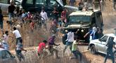 Pengunjuk rasa Palestina melempari kendaraan lapis baja Israel saat berdemonstrasi di Ramallah, Tepi Barat, Kamis (17/10/2019). Pengunjuk rasa menentang pembangunan pos terdepan Israel di dekat desa Palestina, Turmus Ayya, dan pemukiman Israel, Shilo. (JAAFAR ASHTIYEH/AFP)