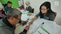 Warga mengisi fomulir pendaftaran Program Samawa Rumah DP 0 Rupiah di lokasi Rusunami Klapa Village, Jakarta, Minggu (28/7/2019). Proses pengajuan permohonan kredit dan pemilihan unit Program Samawa Rumah DP 0 rupiah dimulai dari Sabtu (27/7/2019) sampai 4 Agustus 2019. (Liputan6.com/Herman Zakharia
