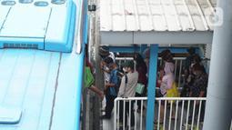 Penumpang menunggu kedatangan bus Transjakarta di Shelter Harmoni, Jakarta, Kamis (5/11/2020). PT Transportasi Jakarta (Transjakarta) menargetkan di tahun 2030 seluruh armada merupakan bus listrik. Diharapkan total bus listrik mencapai 12.120 unit diakhir tahun 2030. (Liputan6.com/Immanuel Antonius)