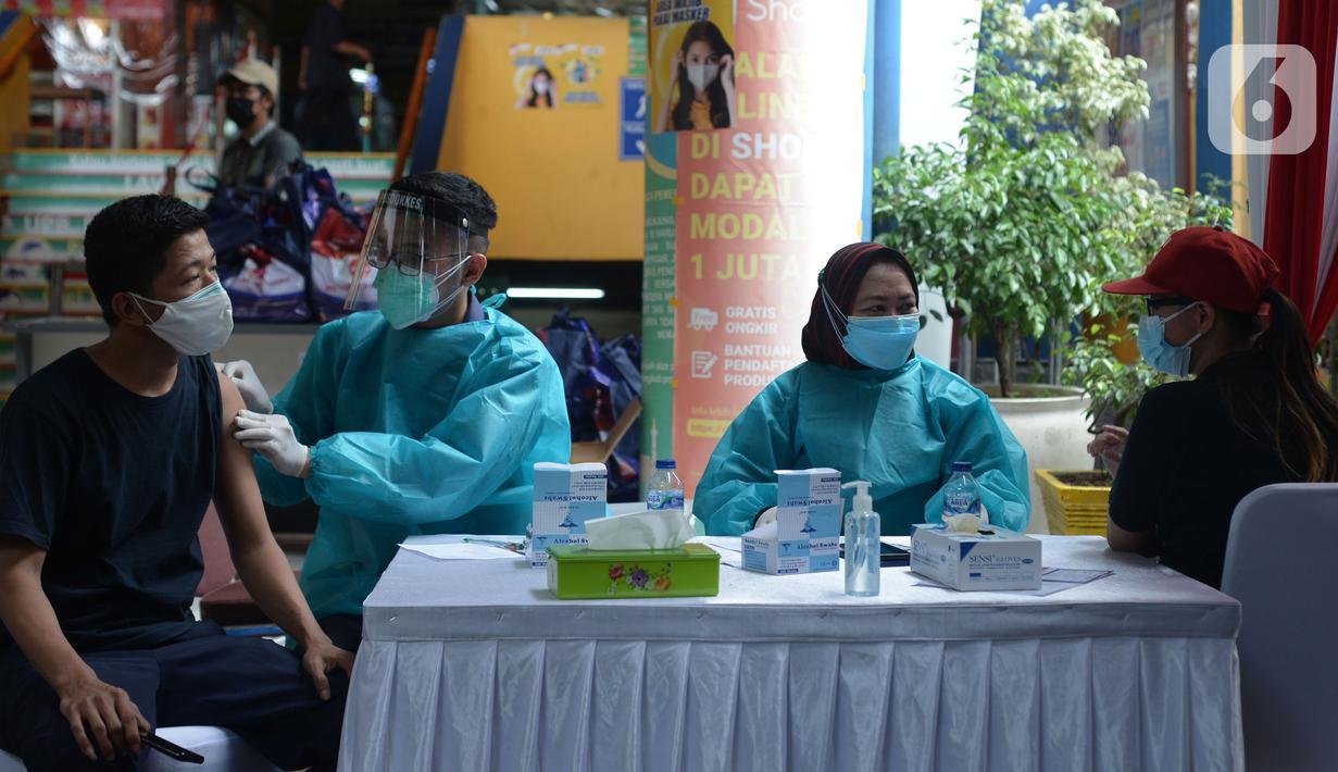 Polisi menyuntikkan vaksin virus corona COVID-19 kepada pedagang Pasar Induk Kramat Jati di Jakarta Timur, Kamis (22/7/2021). Sebanyak 250 pedagang Pasar Induk Kramat Jati menjalani vaksinasi guna menekan penyebaran COVID-19. (merdeka.com/Imam Buhori)