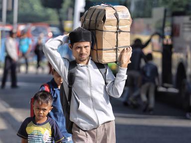 Penumpang berjalan usai turun dari bus Antar Kota Antar Provinsi di Terminal Kampung Rambutan, Jakarta, Selasa (19/6). Empat hari setelah Lebaran, jumlah penumpang yang tiba di Terminal Kampung Rambutan mencapai 17.492 orang. (Liputan6.com/Faizal Fanani)