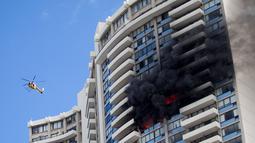 Petugas mengerahkan helikopter untuk membantu proses evakuasi kebakaran yang terjadi di apartemen Marco Polo, Honolulu (14/7). Hingga saat ini tim pemadam kebakaran masih terus berusaha menjinakkan api di apartemen tersebut. (AP Photo / Marco Garcia)