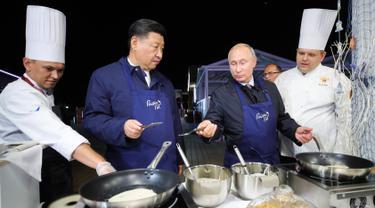 Presiden Rusia Vladimir Putin (dua kanan) berbincang dengan Presiden China Xi Jinping (kedua kiri) saat membuat pancake bersama di sela acara Eastern Economic Forum di Vladivostok, Rusia, Selasa (11/9). (Sergei Bobylev/TASS News Agency Pool Photo via AP)
