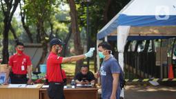 Petugas mengecek suhu tubuh warga di sekitar Taman Lapangan Banteng, Jakarta Pusat, Sabtu (13/6/2020). Mulai hari ini, Taman Lapangan Banteng kembali dibuka untuk umum namun jumlah pengunjung tetap dibatasi sebanyak 200 orang setiap pagi dan sore hari. (Liputan6.com/Immanuel Antonius)