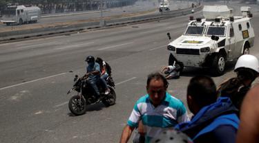 Seorang pengunjuk rasa pendukung oposisi, Luis Alejandro (26) terjatuh saat ditabrak kendaraan taktis Garda Nasional Venezuela di luar pangkalan militer 'La Carlota' di Caracas, Venezuela (30/4/2019). Luis ditabrak oleh tentara yang menghalau aksi demonstrasi tersebut. (Reuters/Ueslei Marcelino)