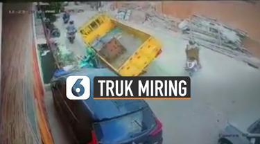 Terekam kamera CCTV sebuah truk miring saat lewati jalanan berlubang.