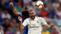 Penyerang Real Madrid, Karim Benzema berebut bola udara dengan pemain Getafe, Leandro Cabrera saat bertanding pada lanjutan La Liga Spanyol di stadion Santiago Bernabeu, Madrid, (19/8). Madrid menang 2-0 atas Getafe. (AP Photo/Andrea Comas)