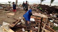 Warga memeriksa kerusakan rumah mereka setelah tsunami menerjang Pantai Carita, di perairan Banten, Minggu (23/12). Data sementara jumlah korban dari bencana tsunami di Selat Sunda tercatat 584 orang luka-luka dan 2 orang dinyatakan hilang. (SEMI / AFP)