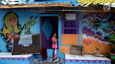 Seorang anak berdiri di depan pintu rumah dengan warna-warni cat dinding dan grafiti di Kampung Bekelir, Babakan Kota Tangerang, Jumat (16/11). Kampung ini dihuni sekitar 300 KK. (Liputan6.com/Fery Pradolo)