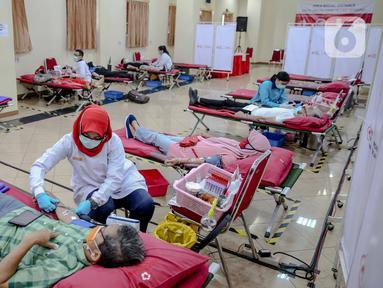 Pendonor sukarela mendonorkan darahnya melalui Unit Tranfusi Darah (UTD) Palang Merah Indonesia (PMI) DKI Jakarta, di Jalan Kramat Raya, Jakarta, Kamis (30/4/2020). (Liputan6.com/Faizal Fanani)