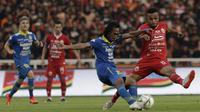Gelandang Persija Jakarta, Yan Pieter, berebut bola dengan pemain Persib Bandung pada laga Shopee Liga 1 di SUGBK, Jakarta, Rabu (10/7). Persija bermain imbang 1-1 atas Persib. (Bola.com/Yoppy Renato)