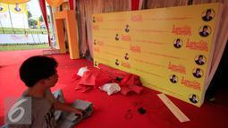 Seorang pekerja melintasi backdroup Ade Komarudin di kawasan alun alun utara Yogyakarta, Jumat (11/3/2016). Ade Komarudin akan mendekalrasikan pencalonan ketua Umum DPP Golkar yang akan bertarung pada Munaslub 2016. (Liputan6.com/Boy Harjanto)