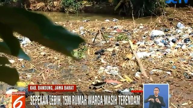 Tumpukan sampah rumah tangga seperti plastik hingga kasur menghambat aliran Sungai Cisangkuy.