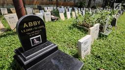 Sebuah batu nisan anjing di pemakaman hewan peliharaan Pondok Pengayom Satwa Jakarta, Senin (8/4). Sebanyak 700 makam di pondok tersebut dirawat dan dipelihara oleh petugas. (Liputan6.com/Fery Pradolo)