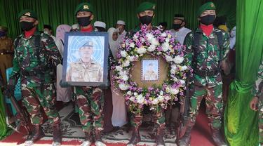 Prajurit TNI memegang foto Pelda Anumerta Rama Wahyudi sebelum dimakamkan di Pekanbaru.