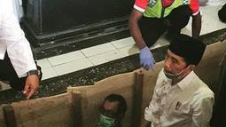 Presiden Joko Widodo atau Jokowi saat berada di liang lahat untuk memakamkan jenazah ibundanya Sudjiatmi Notomihardjo di pemakaman keluarga di Mundu, Kabupaten Karanganyar, Jawa Tengah, Kamis (26/3/2020). Sujiatmi Notomiharjo wafat pada Rabu 25 Maret 2020 pukul 16.45 WIB.  (dok.istimewa)
