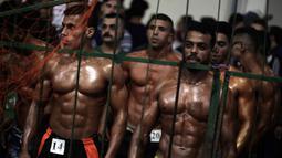 Kontestan Palestina menunggu untuk tampil dalam kompetisi binaraga lokal di Gaza, 26 Oktober 2018. Mereka memamerkan keindahan tubuh berotot di hadapan para juri kontes yang diselenggarakan oleh Federasi Binaraga dan Kebugaran Palestina. (AP/Khalil Hamra)