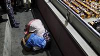 Terpidana kasus dugaan pelanggaran UU ITE sekaligus korban pelecehan seksual Baiq Nuril sujud syukur bersama putranya setelah DPR menyetujui amnesti untuk dirinya dalam sidang paripurna di Kompleks Parlemen Senayan, Jakarta, Kamis (25/7/2019). (Liputan6.com/JohanTallo)