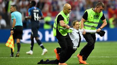 Petugas mengamankan seorang wanita yang menyusup masuk ke lapangan dalam laga final Piala Dunia 2018 antara Prancis dan Kroasia di Luzhniki Stadium, Minggu (15/7). Empat orang berlari masuk ke dalam lapangan menggangu jalannya laga. (AP/Martin Meissner)