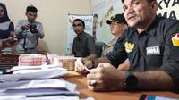 Ketua Bawaslu Pekanbaru Indra Kholid dengan uang diduga untuk serangan fajar di meja hasil tangkapan anggotanya. (M Syukur/Liputan6.com)