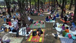 Sebagian pengunjung berkumpul di bawah rimbun pepohonan, Ragunan, Jakarta, Jumat (6/5). Mereka menggelar tikar seraya menikmati bekal makanan yang mereka bawa. (Liputan6.com/Helmi Afandi)