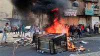 Pengunjuk rasa antipemerintah membakar sejumlah benda dan memblokir jalan saat menggelar protes di Baghdad, Irak, Rabu (2/10/2019). Pengunjuk rasa memprotes korupsi, kegagalan memenuhi layanan publik serta pengangguran. (AP Photo/Hadi Mizban)