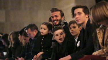 Mantan pesepakbola, David Beckham duduk di barisan depan bersama anak-anaknya Harper, Cruz, Romeo dan Brooklyn menyaksikan koleksi busana terbaru milik sang istri Victoria Beckham Fall/Winter 2016 di New York Fashion Week (14/2). (REUTERS/Andrew Kelly)