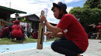 Warga memukul kentongan sebagai peringatan untuk waspada gempa dan tsunami. adegan itu bagian dari simulasi pengurangan risiko bencana di desa Wani II Donggala, yang digelar warga bersama Yayasan Arkom Indonesia, Sabtu (18/7/2020). (Foto: Liputan6.com/ Heri Susanto).