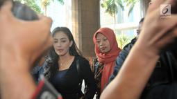 Terpidana kasus pelanggaran ITE Baiq Nuril Maknun (kanan) didampingi politikus PDIP Rieke Diah Pitaloka tiba di Kantor Kemenkumham, Jakarta, Senin (8/7/2019). Guru honorer itu divonis 6 bulan penjara dan denda Rp 500 juta atas perekaman pelecehan seksual yang dialaminya. (merdeka.com/Iqbal Nugroho)