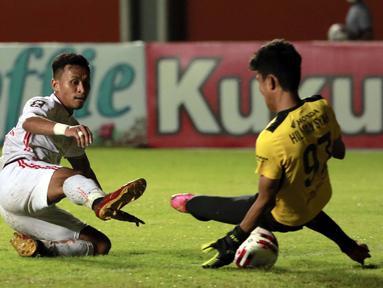 Kiper PSM Makassar, Hilman Syah (kanan) berhasil menghadang tendangan gelandang Persija Jakarta, Osvaldo Haay dalam laga leg pertama semifinal Piala Menpora 2021 di Stadion Maguwoharjo, Sleman, Kamis (15/4/2021). (Bola.com/Ikhwan Yanuar)