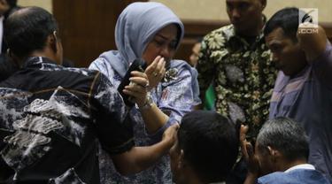 Terdakwa dugaan suap DPRD Sumatera Utara, Tiaisah Ritonga menangis usai menjalani sidang pembacaan putusan di Pengadilan Tipikor, Jakarta, Kamis (14/02). Tiaisah divonis bersalah, dihukum empat tahun dan denda Rp100 juta. (Liputan6.com/Helmi Fithriansyah)