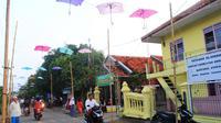 Payung berhias dengan lampu kerlap-kerlip menggantung di atas jalanan Blok Dodog, Desa Sendang, Kecamatan Karangampel, Kabupaten Indramayu. (Liputan6.com/Panji Prayitno)