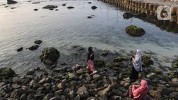 Wisatawan berfoto di kawasan Pantai Anyer, Banten, Sabtu (5/9/2020). Pantai Anyer sempat mampu menarik pengunjung setelah renovasi, namun kembali sepi akibat adanya pandemi COVID-19. (Liputan6.com/Johan Tallo)