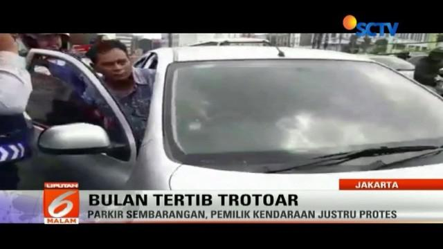 Bukannya taat aturan dan minta maaf, pemilik mobil ini malah memukul petugas, saat kendaraannya akan ditertibkan karena parkir sembarangan.