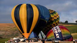 Orang-orang melihat persiapan balon udara pada festival internasional Sagrantino di kawasan Umbria, Italia, 22 Juli 2018. Puluhan balon udara berkompetisi menghadapi tantangan dalam festival yang memperebutkan piala perak tersebut (AFP PHOTO/TIZIANA FABI)
